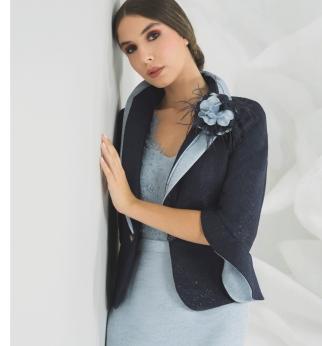 Una giacca dal taglio semplice arricchita dagli inserti bicolore e dal tessuto in lurex
